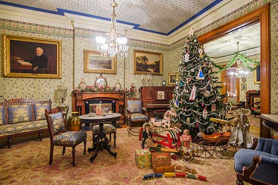 Photograph of harrison's front parlor, fully decorated with a large festive tree, ready for the holidays.