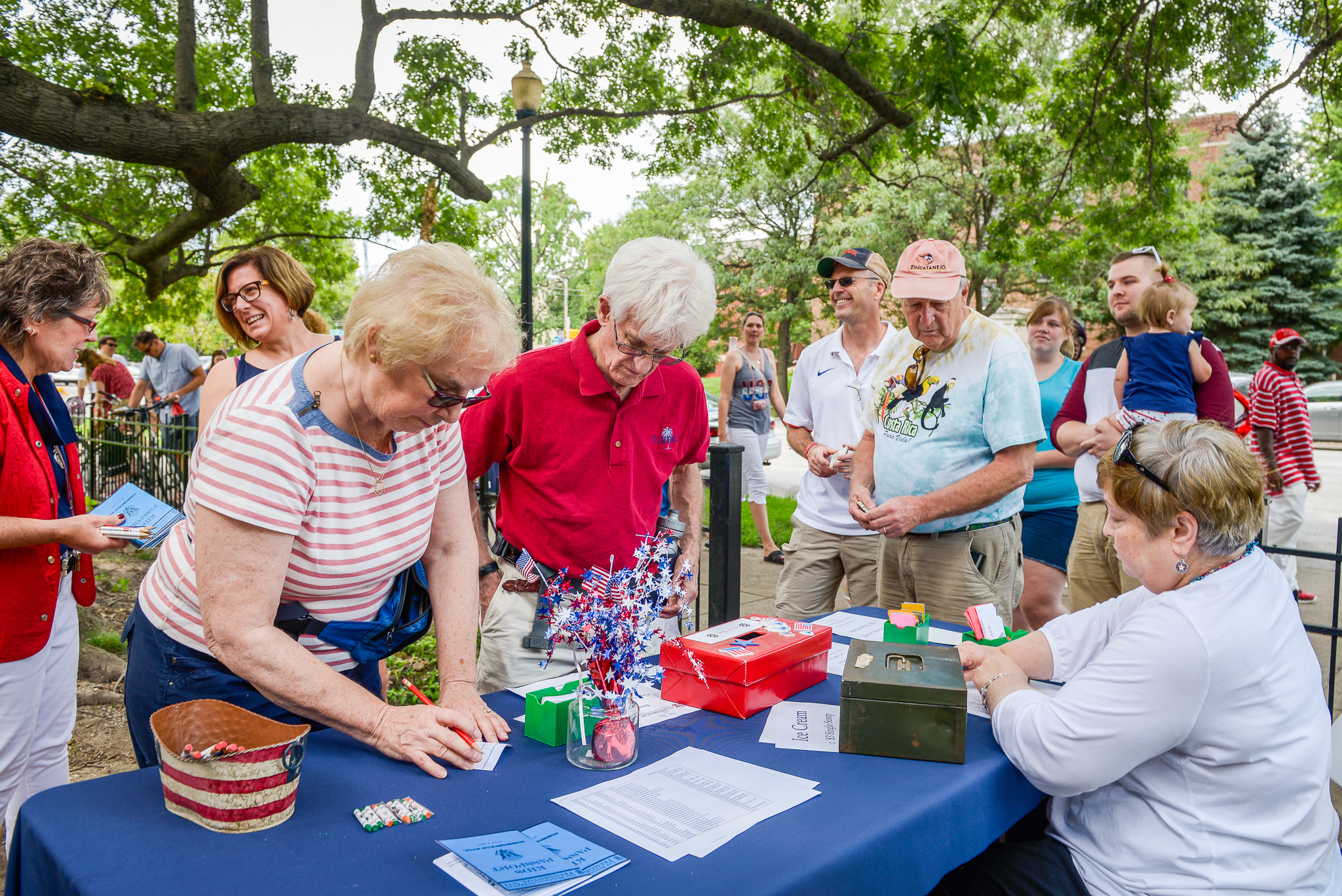 Photo of several seniors gathered at a table, perusing the items while a vendor looks on.