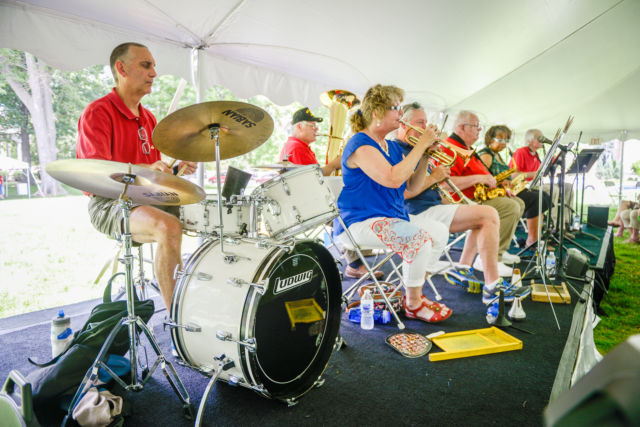 photograph of a live band performing at a presidential site event. band includes a drummer and a brass section.