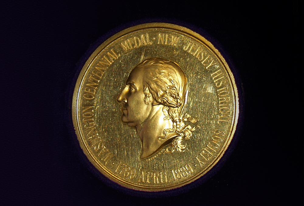 Photograph of an old golden coin inlaid with an image of george washington. The coin is intricately crafted and engraved.