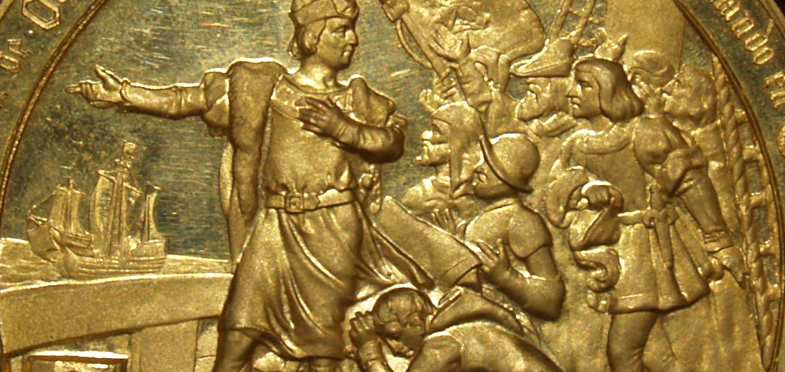 Photographic image of a close up of a gold coin with a depiction of Christopher Columbus.
