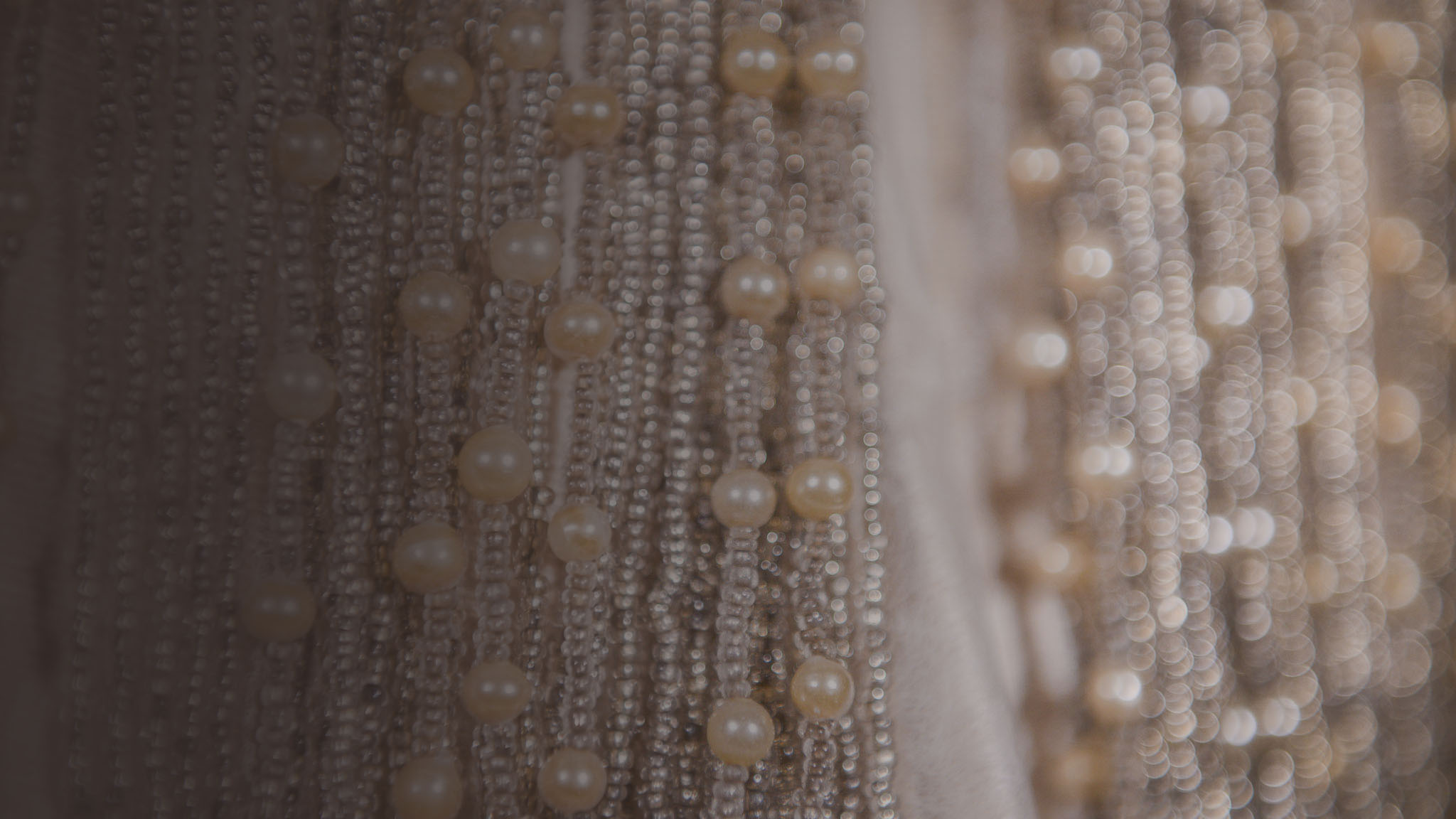 Photographic image of many strands of pearls and beads.