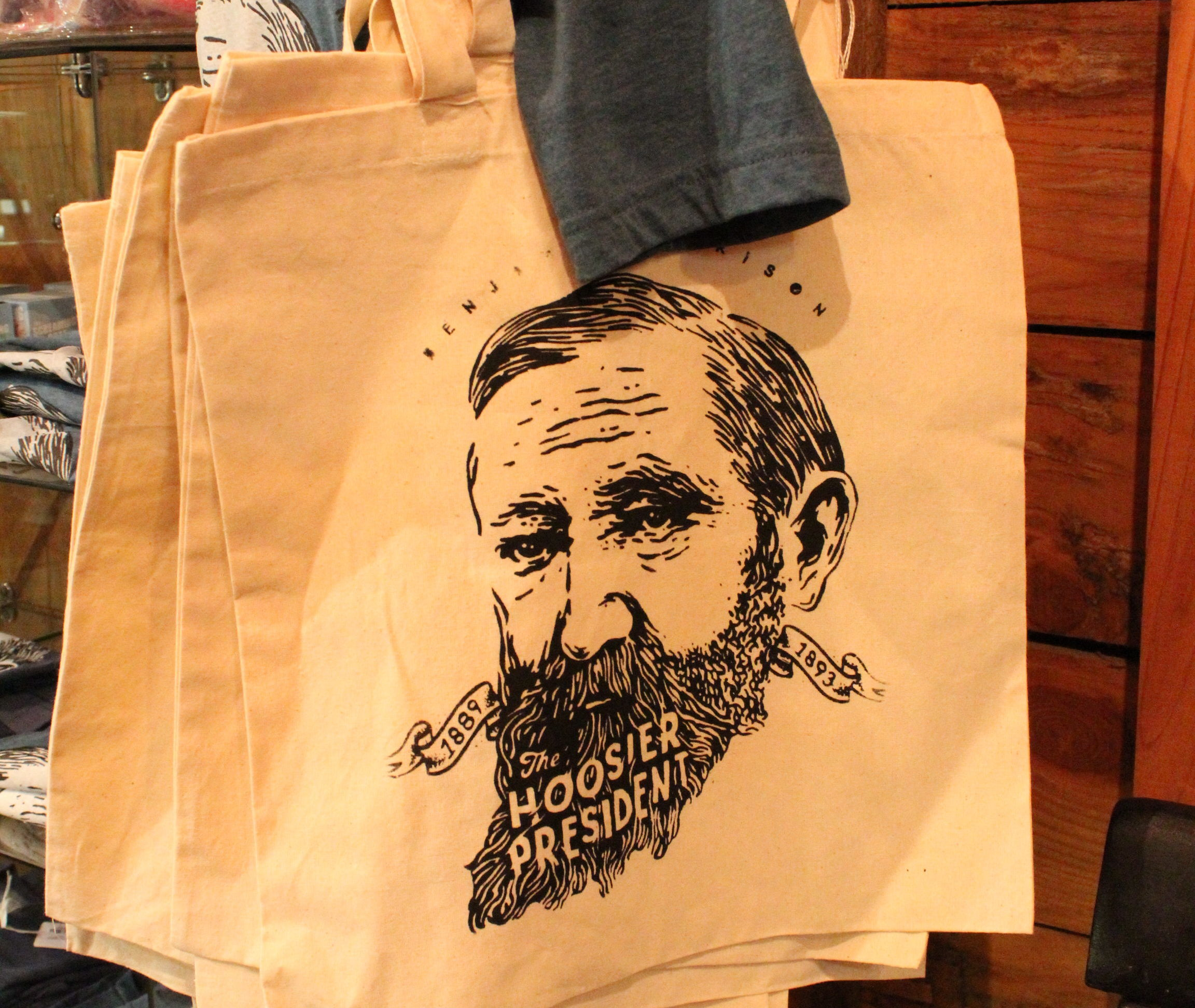 "A photograph featuring an tote bag sold at the presidential site gift shop, emblazoned with an artful illustration of Benjamin Harrison's face. There is text in the negative space in his beard, reading ""The hoosier president""."