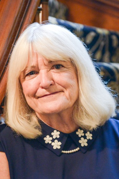 Photograph of Hazel Gillaspy. She is an elderly women wit platinum blonde hair. She wears a blue blouse with a collar that is embroidered with a floral design with a pearl necklace underneath. She has light colored eyes.