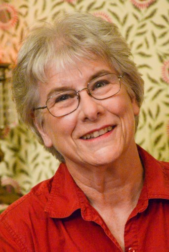 Photo of Jill Whelan, an elderly woman with short platinum blonde hair and ovular glasses. She wears a red dress shirt and smiles in front of a floral patterned wallpaper.