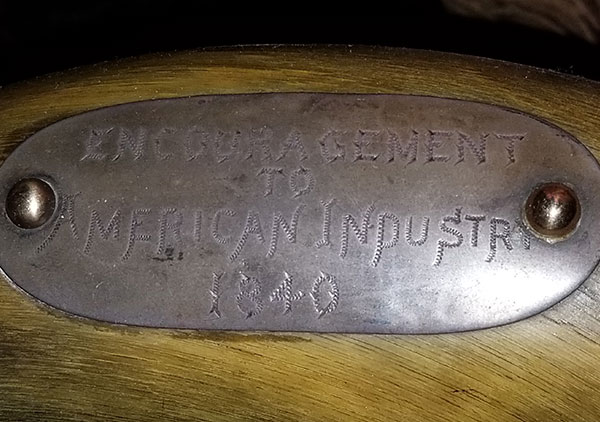Several plaque on the back and arms of the chair convey the following: Top plaque: