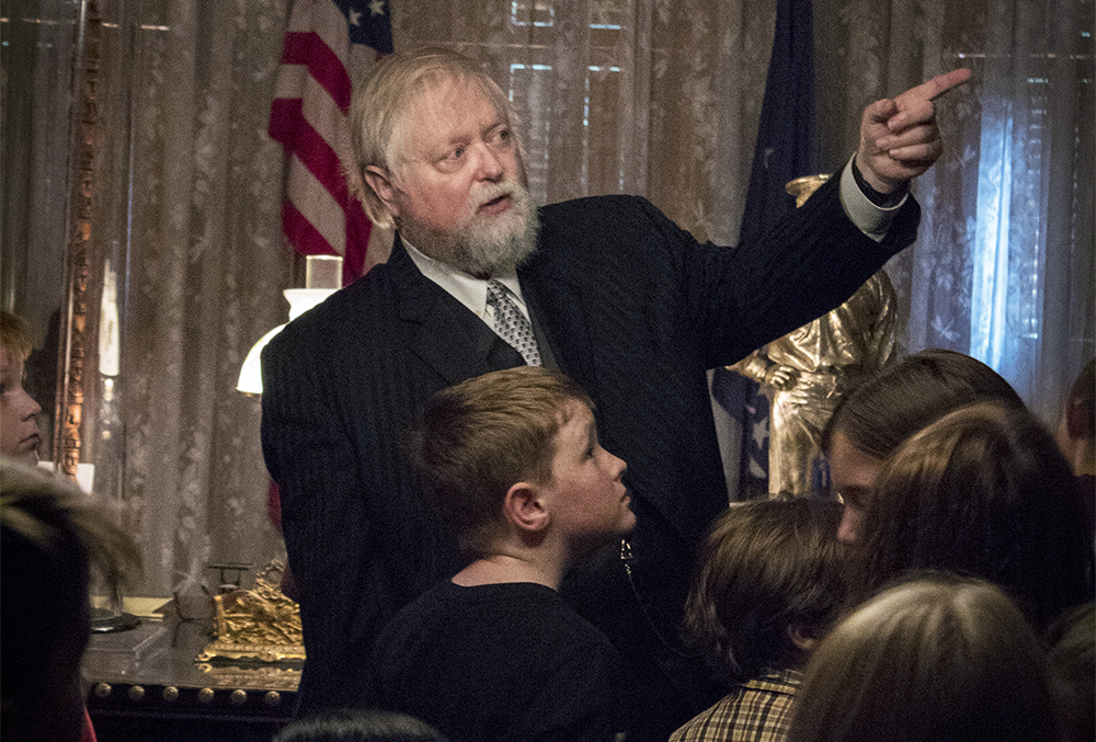 Photographic image of a Benjamin Harrison enactor speaking with school kids. He is pointing towards something on the wall while speaking to some children.