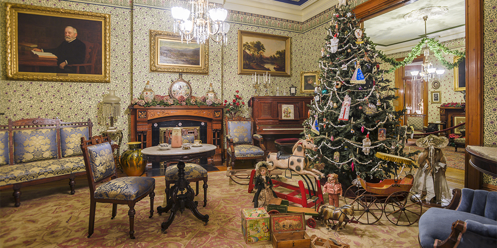 Photograph of the Harrison's front parlor with a decorated christmas tree and presents.