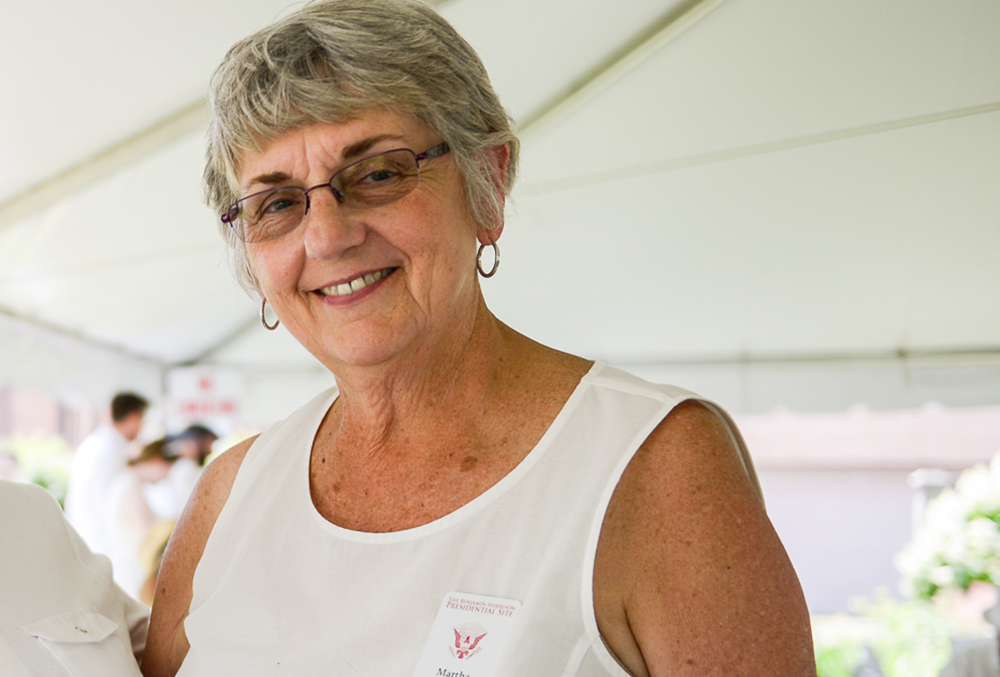 Photo of Martha, president of the volunteer board. She is dressed in white, outdoors during a presidential site event in the spring.