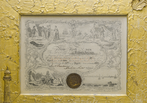 Framed Certificate New York Marine Society in wooden frame. Embellishments on frame: eagle at top center, rope knot in upper left corner, anchor and rope in lower right corner, bust of George Washington with leaf and berry design around Washington. Inner frame wooded frame is gold leaf and a shell in upper right and lighthouse on lower left. The outside edge of the frame is rope painted and linked chain design on inner part of outer frame. 9