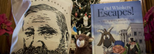 This photograph features Benjamin Harrison merchandise, including a tote bag sporting an illustration of Benjamin Harrison's face, a plush of Benjamin Harrison's pet goat, Old Whiskers, and a children's book about Old Whisker's escape.