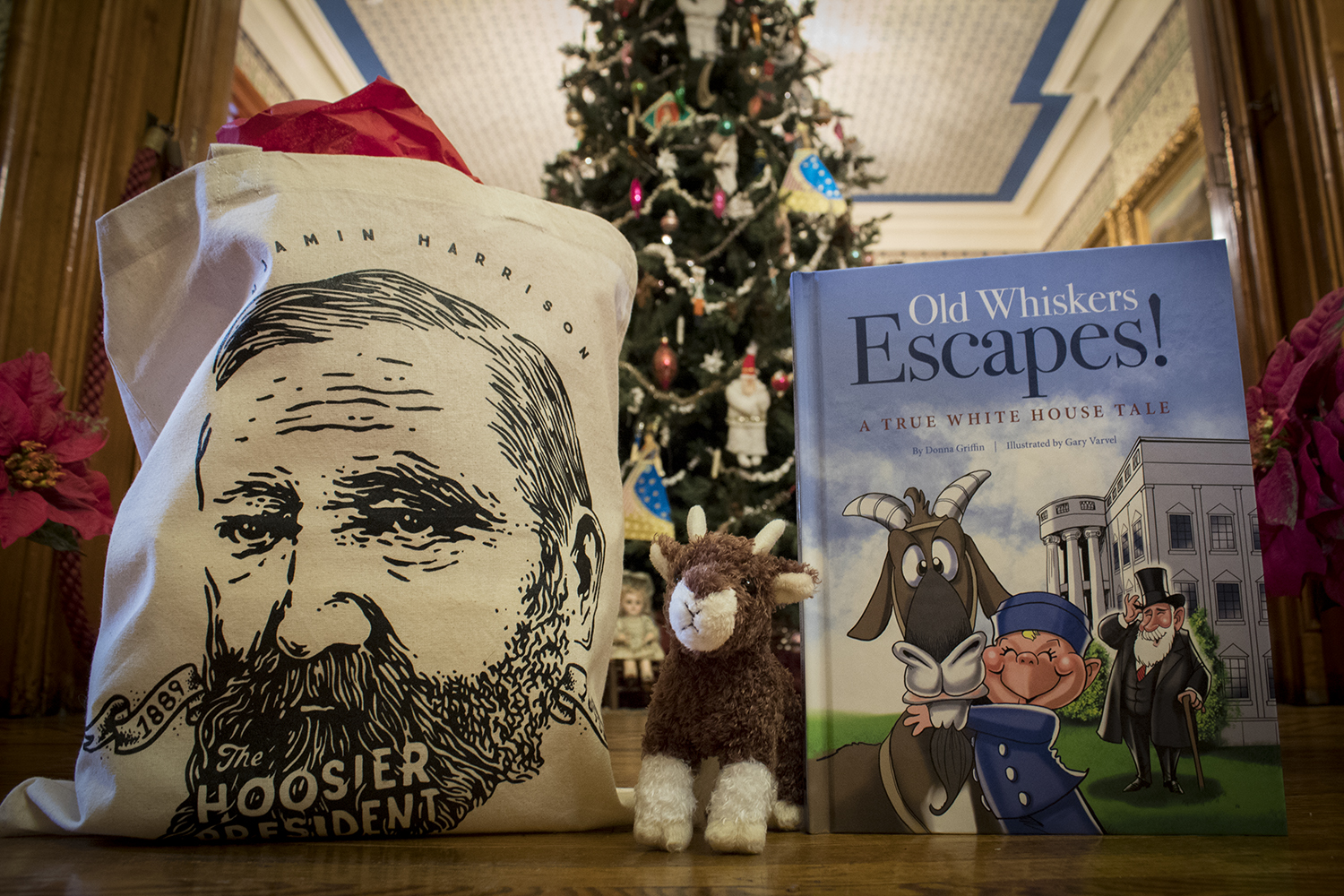 This photograph features Benjamin Harrison merchandise, including a tote bag sporting an illustration of Benjamin Harrison's face, a plush of Benjamin Harrison's pet goat, Old Whiskers, and a children's book about Old Whisker's escape. Pictured in front of a holiday tree, fully decorated with ornaments and tinsel.