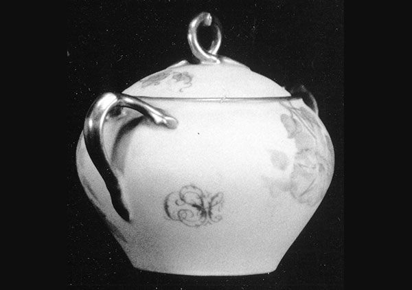 backside of the tea pot. shows a closer look at some of the floral patterning and twig shaped handle.