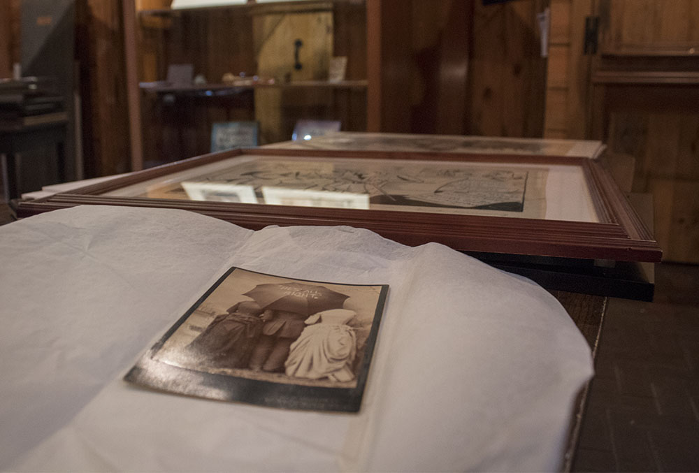 Photographic image of a photograph on a table. Museum cases are in the background.