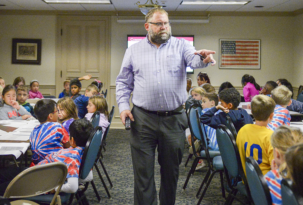 Photo of Roger Hardig teaching a group of school kids.