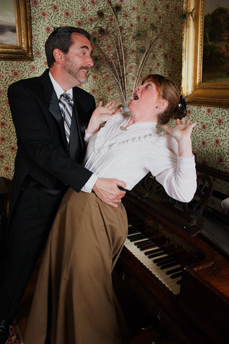 photograph of two candlelight theater actors in a room in the presidential manor. one is a woman, falling back towards a piano as if to faint, while a man catches her.
