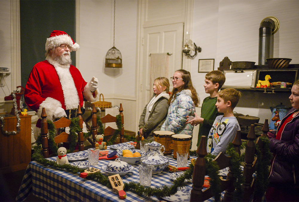 photo of santa clause talking to a group of kid's in the benjamin harrison home's kitchen.