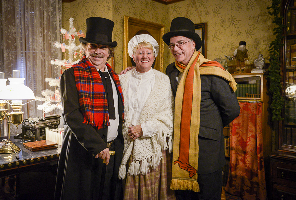 Photograph of a trio of Candlelight Theatre actors, captured in the office of the Benjamin Harrison home. They're dressed for the Twas the night before performance.
