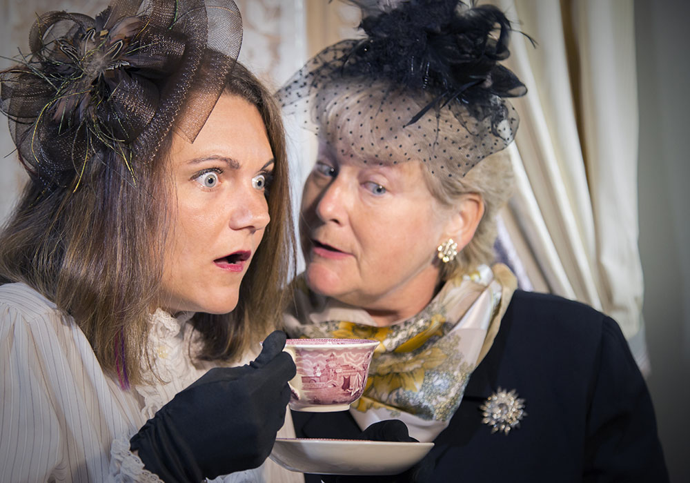 This image shows two actors in the candlelight theater. The pair appear to be dressed in funeral attire. On the left is a younger woman with an expression of great fright, holding a teacup on a saucer. Next to hear is an elderly woman with light hair, who appears to be whispering in her ear