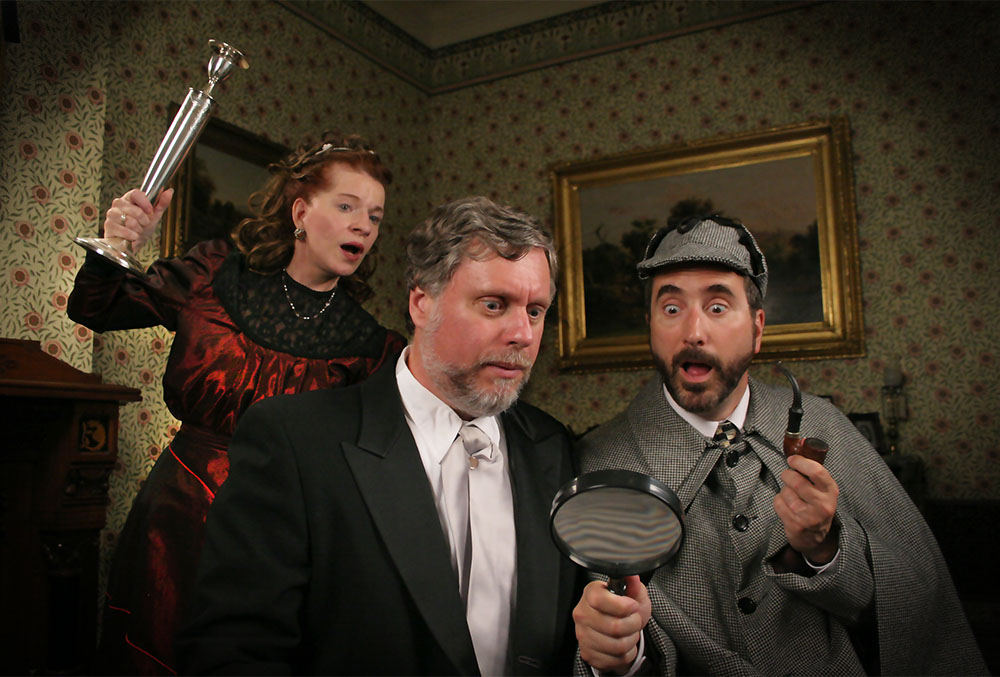 Photo of three candlelight theatre actors in the middle of a performance. The photo depicts Sherlock holmes and Watson in a dark room. Holmes holds a pipe in his hand, and wears an expression of surprise as watson looks onward with a magnifying glass. Unbeknownst to them, there is a woman dressed in red behind them with a candlestick, preparing to attack them.