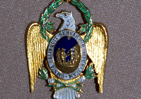 Photo of harrison's badge. bears a predominantly light blue ribbon, with white edging, holding an eagle with golden wings and wreath around head. The center is a picture of figures against a blue background, encircled by the text