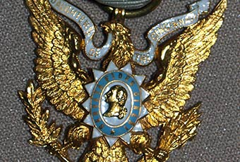 Daughter of the Cincinnati badge. Predominantly white ribbon with blue edging holding a golden eagle. An emblem in the center of the eagle contains a golden bust of a male figure and is encircled by the text