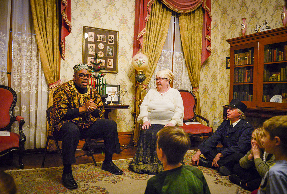Photograph of kids listening to Candlelight Theatre actors.