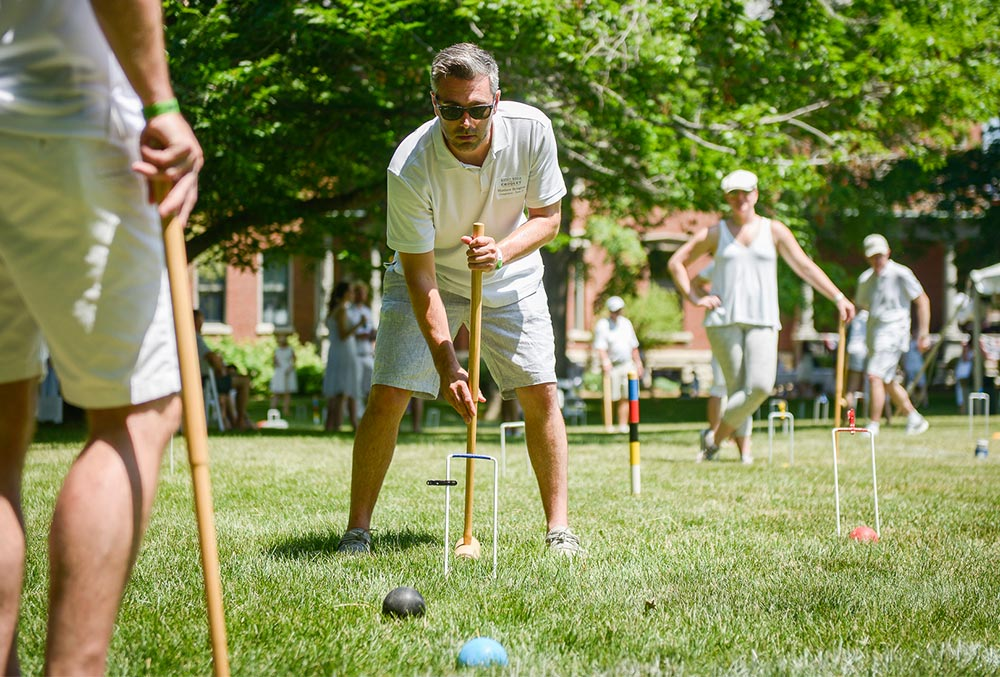 photo of a crowd of people playing croquet on the presidential lawn on a summers day.