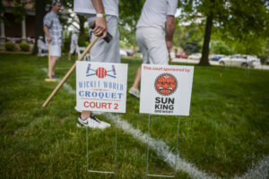 Photograph of people playing croquet on the lawn of the Presidential Site, all dressed in white on a warm sunny day.