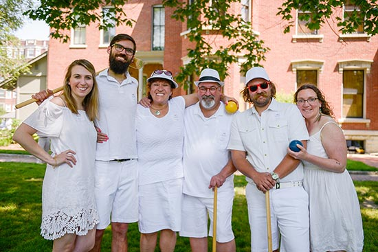 photo of six people happily gathered outside the benjamin harrison home. they are dressed in white, attending the wicket world of croquet.
