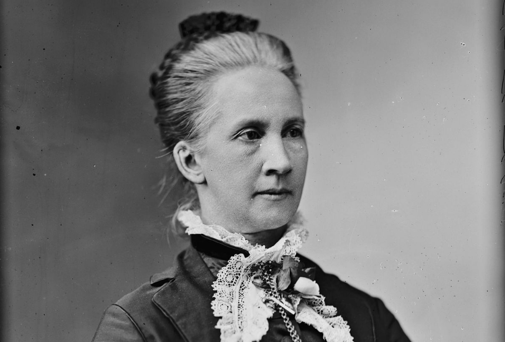 Photo of Belva Lockwood, dressed darkly with small white frills at the neck. Her hair is loosely bunned and braided with a black hairpin. She intensely looks out of frame, to the right of the photographer.