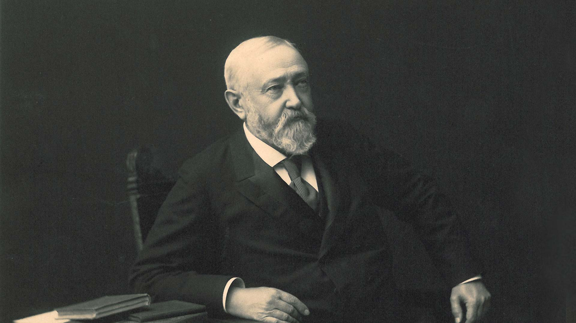 Benjamin Harrison seated in a chair with a table