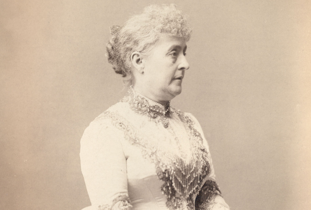 Sepia-toned photographic image of Caroline Harrison in her inaugural dress which has a large bustle and beading on the bodice and around the neck. Caroline is wearing gloves and holding a fan; her hair is pulled back from her face. She is standing in front of a large bookcase and is resting her hands in the back of a chair, while holding a fan and kerchief.