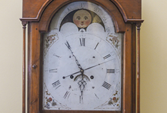 Tall case or grandfather clock made by George Woltz in Hagerstown, Maryland between 1800 and 1812. Clock has moon dial at top and a date dial below the center of the hands, and strikes on the hour. Cherry cabinet with front legs that curve out . There is a spindle on either side of the face. Rounded center at the top with rosette design. Top corners come up to pointed spindles. Clock face is a half circle at top with the dates above the moon dial, Roman numerals and painted floral designs in four corners, and glass door.