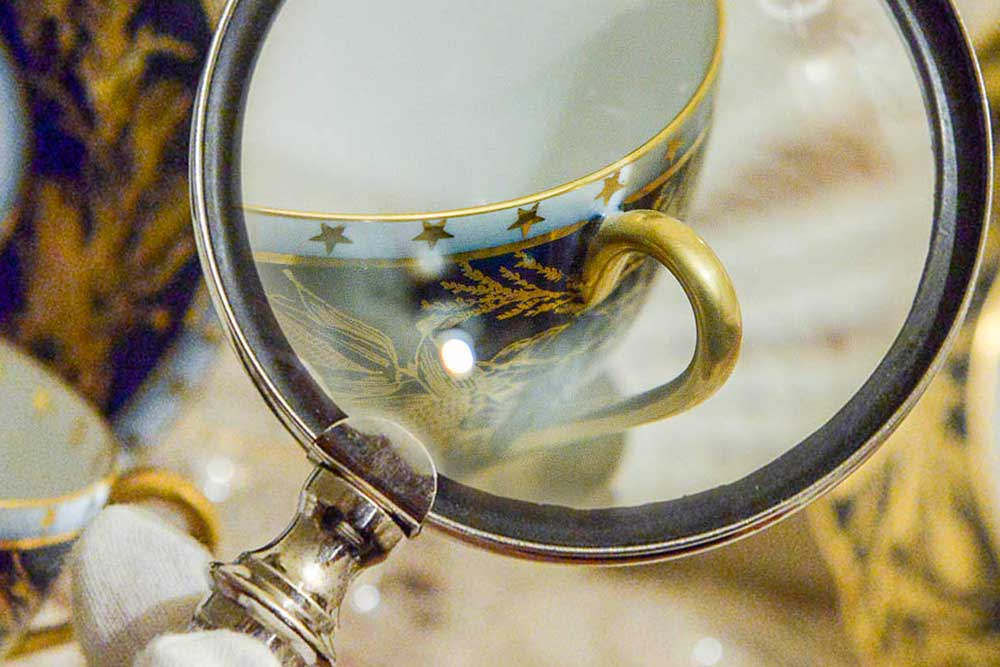 Photograph of a magnifying glass enhancing the detail on a coffee cup. The cup is inlaid with gold details depicting tree branches and stars, as well as a gold trim around the lip of the cup and handle.