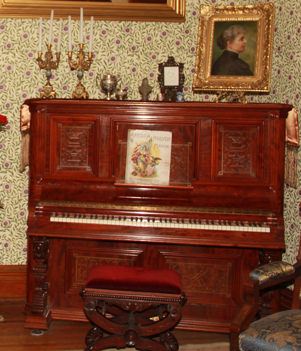 Wooden upright piano. There is a silver plaque mounted above the keyboard with manufacturer's name and information. The wood panels on each side of front have an incised design. Center panel has incised design of violin and mandolin crossed surrounded by flowers and leaves.