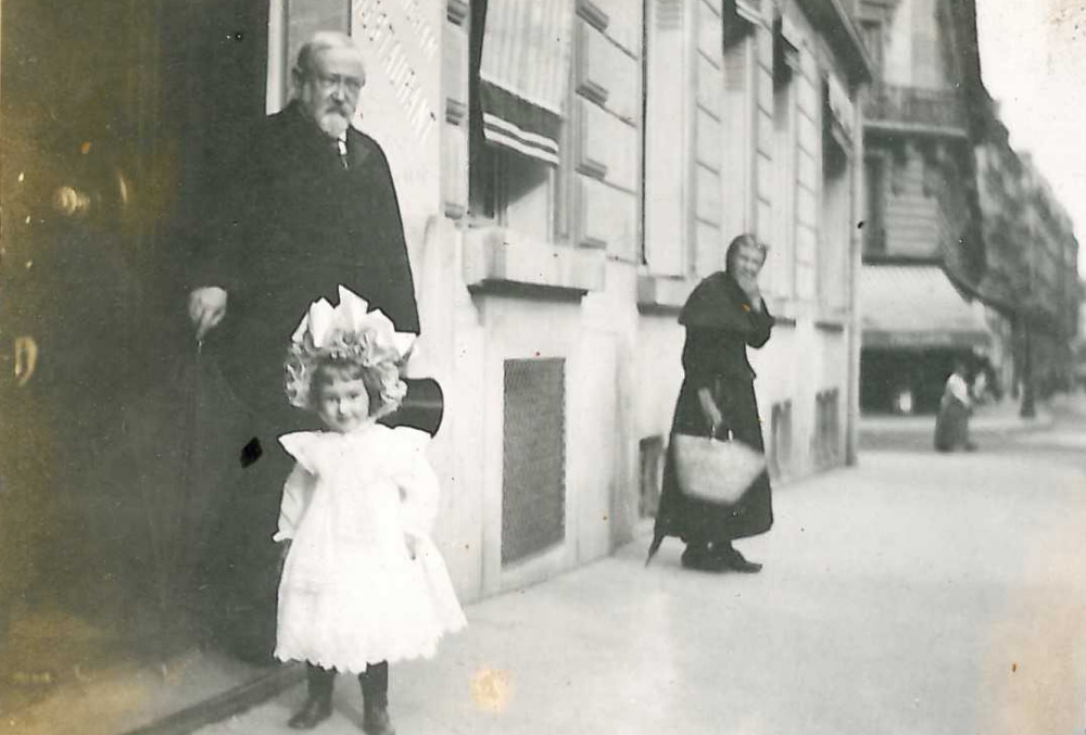 Photograph of Benjamin Harrison and his daughter, Elizabeth Harrison Walker, on a street in Paris. Benjamin Harrison steps out of a building with his cane in his right hand, and his top hat in his left. Elizabeth wears a frilly white dress and a frilly white hat. Slightly out of focus in the background is a woman carrying a tote bag with an expression of surprise at seeing Benjamin Harrison.