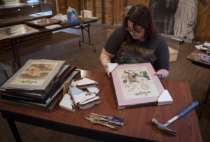 Photograph of curator Emily Hannawalt, carefully framing a picture at a desk. On the desk lies a pile of frames, a hammer, screwdriver, pliers, and a stack of pictures.