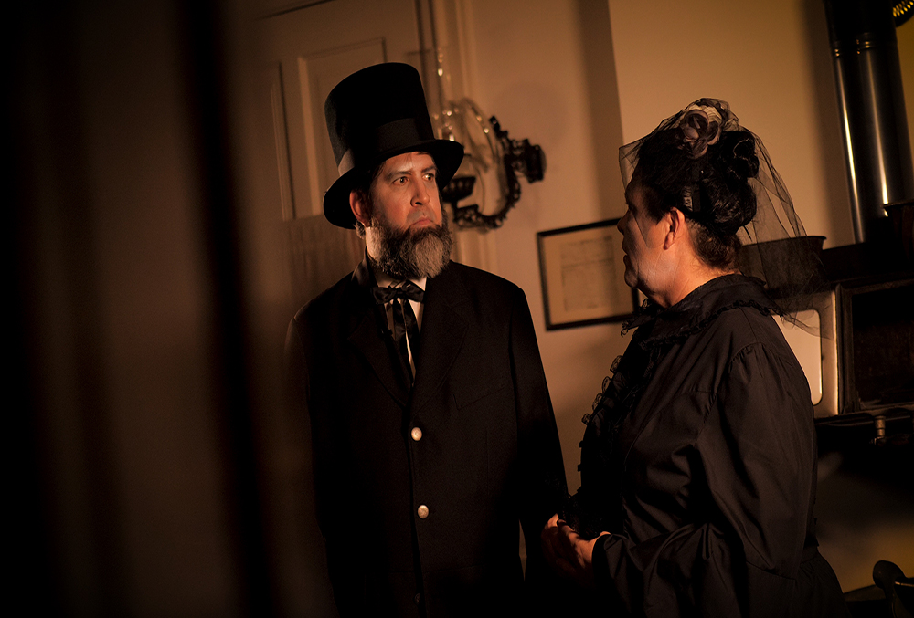 Photograph of two actors during the ghost tales of the civil war performance. One male, one female. The male is dressed as abraham lincoln, and the female is dressed as mary todd lincoln.