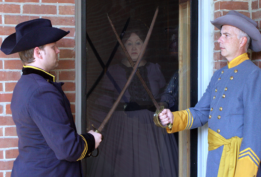 Photograph of two actors from ghost tales of the civil war. The photo shows a union soldier classing swords with a confederate soldier, while a woman looks on in the background.