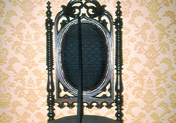 Gothic or Elizabethan rival chair circa 1850 that belonged to the Harrison family. It has been reupholstered in horse hair fabric with a diamond pattern. Back of chair is an oval shape with carved top ornament and side spooled spindles. Legs are also spooled spindles.