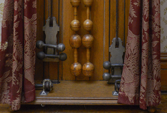 Oak case with iron dumbbell shaped weights (5) on ropes to be pulled, eight sets of wooden dumbbells and pair of Indian clubs. Metal plate: