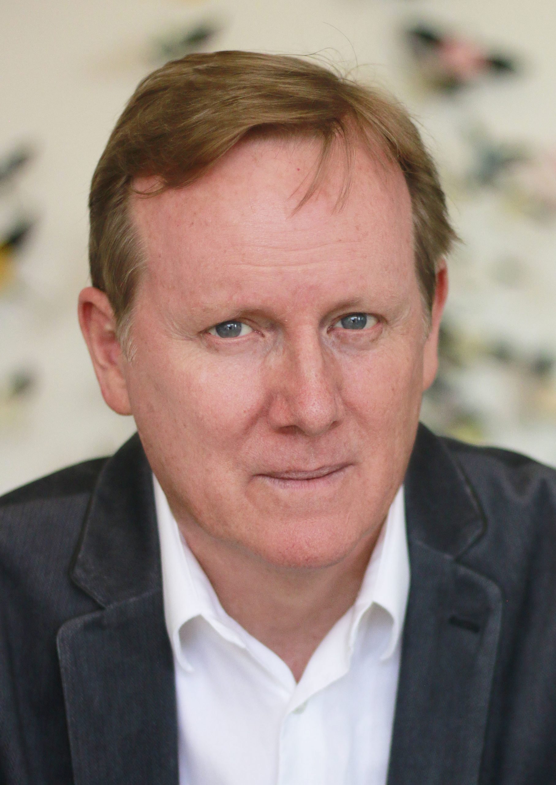 Portrait of Dave Surina. A middle aged man with light brown hair and green eyes. He wears a black jacket with white dress shirt, in front of an out of focus floral background.