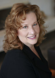 Portrait of Anne Surina. She is middle aged with reddish brown hair and green eyes. She smiles at the camera and wears a black dress jacket.