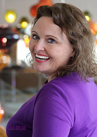 Portrait of Judy Lombardo, a middle aged woman wearing a purple cardigan. She looks over her shoulder with a big gleeful smile. She has brown hair and blue eyes.