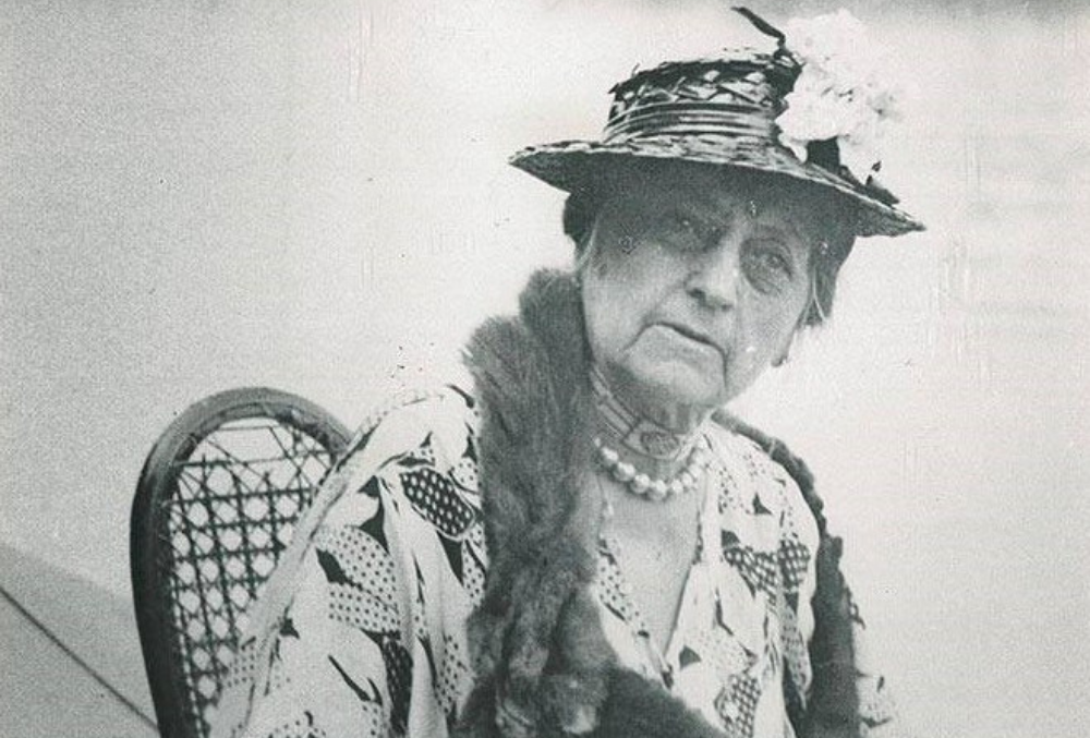 Photo of Mary Dimmick Harrison, pictured seated in a wooden woven chair, wearing a patterned blouse, fox pelt scarf, pearl necklace, and woven hat with a corsage.