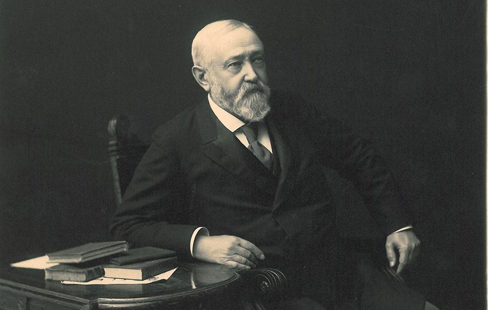 Photographic image of Benjamin Harrison sitting in a chair. There is a side table next to him with several books