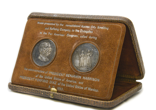 A brown box that has the appearance of being made from snakeskin; box opens up and medals swing out to prop the top up as a display case; two medals inside-one is intended for the President of the United States of America and the other is intended for the President of the United States of Mexico. Marked: